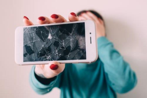 Girl Holding Broken Cell Phone with red fingernails